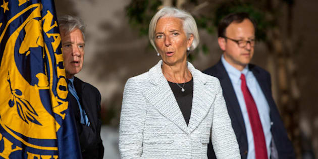 WASHINGTON, DC - APRIL 30, 2014: International Monetary Fund Managing Director Christine Lagarde, center, walks with IMF chief spokesman Gerry Rice, left, before announcing a two-year 'Stand-By Arrangement' for Ukraine at IMF headquarters on April 30, 2014 in Washington D.C. The IMF intends for the $17 billion fund to restore stability and launch economic growth in the country.  (Photo by Allison Shelley/Getty Images)