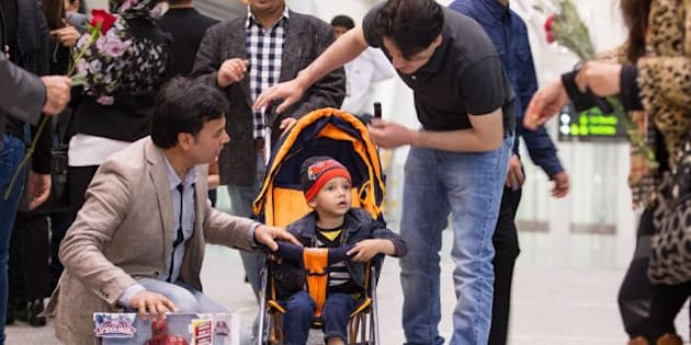 Family and well wishers shower young Abuzar Ahmad with presents and flowers as he arrives at Pearson airport in Toronto, Ontario, Canada, April 30, 2014.  Miracle child Abuzar Ahmad, the only surviving child of Sardar Ahmad, the AFP reporter who was killed with his family six weeks ago in an attack on a Kabul hotel,  arrived in Canada to start his life anew.     AFP PHOTO / Geoff ROBINS