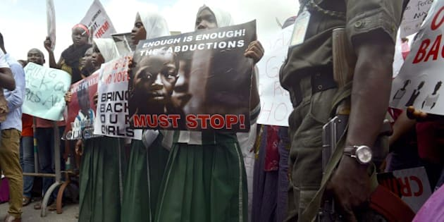 A policeman stand beside children holding as members of Lagos based civil society groups hold rally calling for the release of missing Chibok school girls at the state government house, in Lagos, Nigeria, on May 5, 2014. Boko Haram on Monday claimed the abduction of hundreds of schoolgirls in northern Nigeria that has triggered international outrage, threatening to sell them as 'slaves'. 'I abducted your girls,' the Islamist group's leader Abubakar Shekau said in the 57-minute video obtained by AFP, referring to the 276 students kidnapped from their boarding school in Chibok, Borno state, three weeks ago. AFP PHOTO / PIUS UTOMI EKPEI        (Photo credit should read PIUS UTOMI EKPEI/AFP/Getty Images)