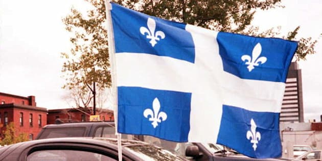 MONTREAL, CANADA:  A car stopped at a street light in Montreal waves the flag of the province of Quebec the day of the referendum on Quebec separatism 30 October. Quebecers vote 30 October on whether they want to remain in Canada or form their own nation.       AFP PHOTO (Photo credit should read CARLO ALLEGRI/AFP/Getty Images)
