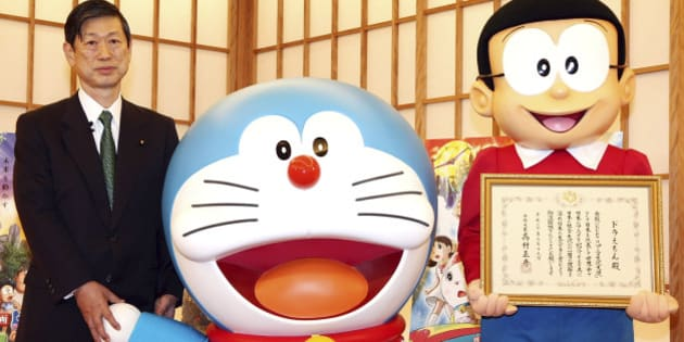 TOKYO - MARCH 19:  (L to R) Japanese Foreign Minister Masahiko Komura, Japanese popular cartoon characters Doraemon and Nobita-kun attend the Anime Ambassador inauguration ceremony at the Ministry of Foreign Affairs on March 19, 2008 in Tokyo, Japan. Doraemon, the fictional robotic cat, will be the first 'anime ambassador', and is intended to promote popular Japanese culture abroad.  (Photo by Junko Kimura/Getty Images)