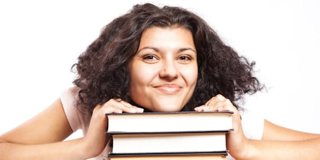 A university student with her head on her books giving a big smile