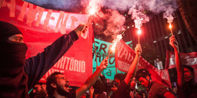 SAO PAULO, BRAZIL - MAY 15, 2014: Black Bloc protesters Group clash with policemen during a protest against the World Cup on the evening of Thursday, May 15, 2014 in Sao Paulo, Brazil. Protests are taking place in various cities of the country and questioned the high spending on construction of stadiums and fight for better conditions and budget for health and education.  (Photo by Victor Moriyama/Getty Images)