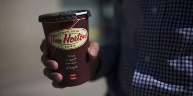 A customer holds a coffee cup outside a Tim Hortons Inc. restaurant in Toronto, Ontario, Canada, on Monday, Sept. 16, 2013. Tim Hortons Inc. Chief Executive Officer Marc Caira said Canadas largest coffee and doughnuts chain must succeed in the U.S. as competition brings slower growth at home. Photographer: Brent Lewin/Bloomberg via Getty Images