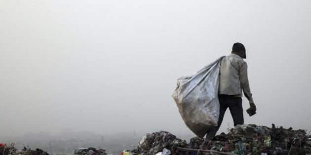 A rag picker carries a sack of sorted recyclable materials collected from garbage at the Ghazipur landfill site in the east of New Delhi, India, on Friday, May 30, 2014. New Delhi, whose population will reach almost 21 million by 2015, generates 8,000 tons of garbage a day. Trash is not separated between organic and inorganic materials -- everything from leftover food to batteries and beverage cans goes into Indian bins -- hurting efficiency and raising toxic emissions. Photographer: Udit Kulshrestha/Bloomberg via Getty Images
