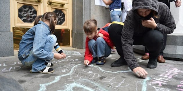 Children, refugees from Crimea and from eastern Ukrainian regions, draw symbolic maps depicting their regions and cities, on the sidewalk at the entrance of Ukrainian parliament in Kiev during a rally on June 5, 2014. At least 10,000 people have been driven from their homes since the start of the Ukraine crisis, with Crimean Tatars the hardest-hit, according to the UN refugee agency. AFP PHOTO/ SERGEI SUPINSKY        (Photo credit should read SERGEI SUPINSKY/AFP/Getty Images)