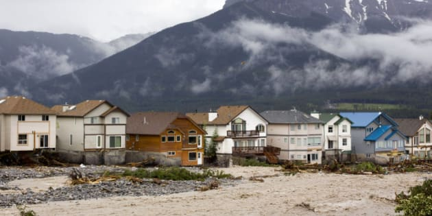 CANMORE, CANADA - JUNE 21:  The houses along the east side of Cougar Creek in front of Three Sisters Mountain suffer damage on June 21, 2013 in Canmore, Alberta, Canada. Widespread flooding caused by torrential rains washed out bridges and roads, prompting the evacuation of thousands.  (Photo by John Gibson/Getty Images)
