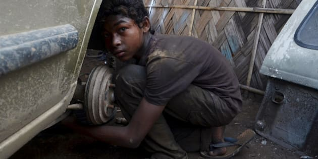 Ural Rahul, 15, works on a car at a repair garage in Dimapur, India's northeastern state of Nagaland, on June 12, 2013, the World Day Against Child Labour. The day, first observed in 2002 and sanctioned by the International Labour Organization (ILO), aims to highlight the plight of children engaged in work that deprives them of adequate education, health, leisure and basic freedoms, violating their rights. AFP PHOTO/CAISII MAO        (Photo credit should read Caisii Mao/AFP/Getty Images)