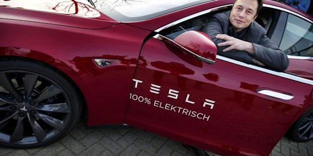 Elon Musk, co-founder and CEO of American electric vehicle manufacturer Tesla Motors, poses with a Tesla during a visit to Amsterdam on January 31, 2014. The European Tesla Service is based in Tilburg and the European headquarters is in Amsterdam. AFP PHOTO / ANP/ JERRY LAMPEN  --NETHERLANDS OUT--        (Photo credit should read JERRY LAMPEN/AFP/Getty Images)