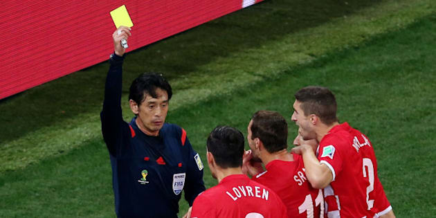 SAO PAULO, BRAZIL - JUNE 12:  Referee Yuichi Nishimura shows Dejan Lovren of Croatia (2nd L) a yellow card and awards a penalty kick during the 2014 FIFA World Cup Brazil Group A match between Brazil and Croatia at Arena de Sao Paulo on June 12, 2014 in Sao Paulo, Brazil.  (Photo by Elsa/Getty Images)
