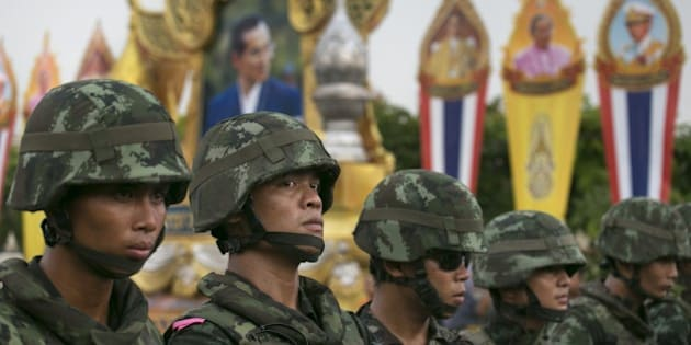 BANGKOK, THAILAND - MAY 26: Thai military stand guard near portraits honoring Thai King Bhumibol Adulyadej during an anti-coup protests as General Prayuth receives the Royal Endorsement as the military coup leader May 26, 2014 in Bangkok, Thailand. Thailand has seen many months of political unrest and violence which has claimed at least 28 lives. Thailand is known as a country with a very unstable political record, it is now experiencing it's 12th coup with 7 attempted pervious coups. Thailand's coup leaders have detained former Prime Minister Yingluck Shinawatra, along with Cabinet members and other anti-government protest leaders for up to a week.
