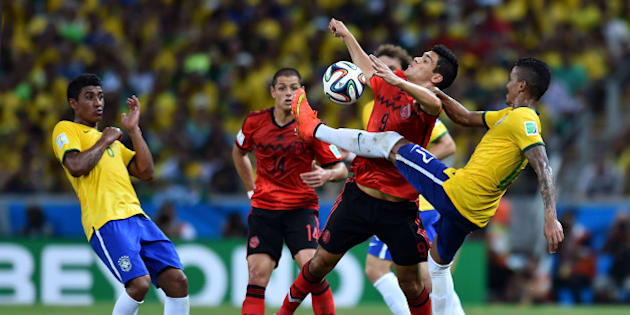 FORTALEZA, BRAZIL - JUNE 17: Luiz Gustavo of Brazil competes for the ball with Raul Jimenez of Mexico during the 2014 FIFA World Cup Brazil Group A match between Brazil and Mexico at Castelao on June 17, 2014 in Fortaleza, Brazil.  (Photo by Buda Mendes/Getty Images)