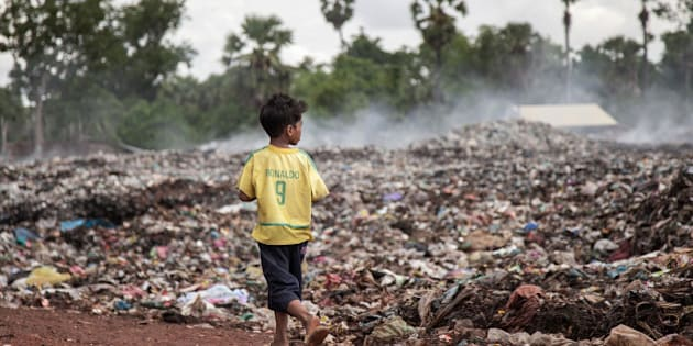SIEM REAP, CAMBODIA - JUNE 11:  A young scavenger wearing a Brazilian national football team t-shirt walks near a burning pile of trash in the Anlong Pi landfill on June 11, 2014 in Siem Reap, Cambodia. Dozens of children work every day in the Anlong Pi landfill, which is situated only few kilometres aways from the world famous Angkor temples, visited by more than 3 million tourists every year. Despite the Cambodian government's commitments and legal responsibilities to end child labor - enshrined in its ratification of relevant international covenants, domestic laws and the implementation of several national policies aimed at ending child labor - it remains a significant concern in Cambodia, where almost a third of the population lives on less than a dollar per day. Child labor is a consequence of this poverty, often resulting from a family's inability to support itself. According to a recent report from the International Labour Organisation (ILO), an estimated 19.1% of the close to 4 million children in Cambodia between the ages of 5 and 17 engage in economic activities. An estimated 56.9% of those children are child labourers, with a third of them being involved in hazardous activities mostly in the agriculture, forestry and fishing sectors. (Photo by Omar Havana/Getty Images)