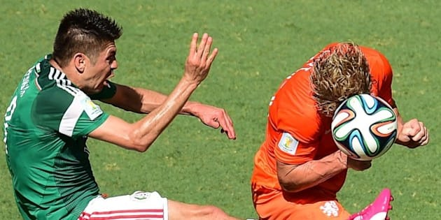 Mexico's forward Oribe Peralta (L) vies with Netherlands' forward Dirk Kuyt during a Round of 16 football match between Netherlands and Mexico at Castelao Stadium in Fortaleza during the 2014 FIFA World Cup on June 29, 2014.   AFP PHOTO/ JAVIER SORIANO        (Photo credit should read JAVIER SORIANO/AFP/Getty Images)
