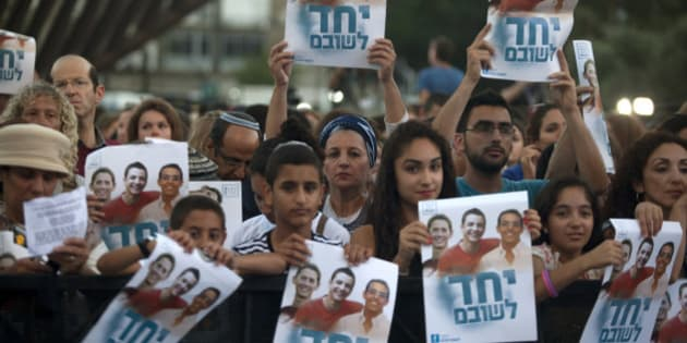 TEL AVIV, ISRAEL - JUNE 29:  (ISRAEL OUT) Israelis hold a poster showing the three missing Israeli teenagers, as they attend a rally under the slogan 'Bring Our Boys Home' on June 29, 2014 in Tel Aviv, Israel.Thousands of people gathered in Tel Aviv's Rabin Square on Sunday evening for a rally calling for the release of the three Israeli teens who were kidnapped more than two weeks ago.  (Photo by Lior Mizrahi/Getty Images)