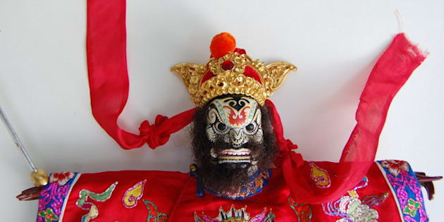 A well known hero in Chinese folklore, he is known for driving out evil and commands 80,000 demons.  He has a red face or red in his face, a fierce black beard and the ear shaped ties for his hat are always prominently depicted.