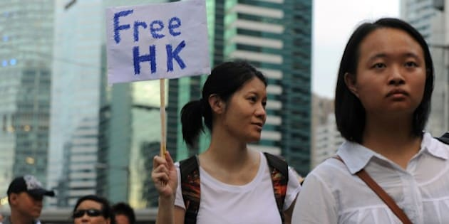 A protester displays a placard during a pro-democracy rally seeking greater democracy in Hong Kong on July 1, 2014 as frustration grows over the influence of Beijing on the city. July 1 is traditionally a day of protest in Hong Kong and also marks the anniversary of the handover from Britain to China in 1997, under a 'one country, two systems' agreement. AFP PHOTO / DALE DE LA REY        (Photo credit should read DALE de la REY/AFP/Getty Images)