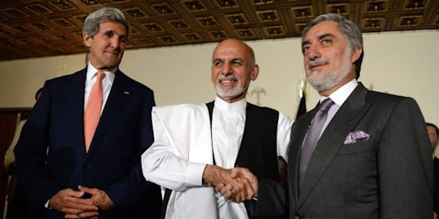 US Secretary of State John Kerry (L) looks at Afghan presidential candidates Ashraf Ghani (C) and Abdullah Abdullah (R) shaking hands, after a joint press conference in Kabul on July 12, 2014.  US Secretary of State John Kerry on July 12 held a second day of talks with Afghanistan's feuding presidential hopefuls, seeking a deal to 'clean up the tally' after disputed elections. AFP PHOTO/SHAH MARAI        (Photo credit should read SHAH MARAI/AFP/Getty Images)