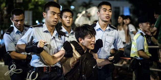 Policemen remove protesters in the central district after a pro-democracy rally seeking greater democracy in Hong Kong early on July 2, 2014 as frustration grows over the influence of Beijing on the city.  Scores of protesters were forcibly removed by police in the early hours following a massive pro-democracy rally which organisers said saw a turnout of over half a million.  AFP PHOTO / Philippe Lopez        (Photo credit should read PHILIPPE LOPEZ/AFP/Getty Images)