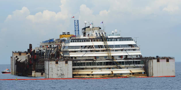 ISOLA DEL GIGLIO, ITALY - JULY 14:  The wrecked ship Costa Concordia is seen having been raised by two meters during the refloating operations on July 14, 2014 in Isola del Giglio, Italy. On the first day of the operation the wreck will be partially refloated by 2 metres from the platfoms that support it and will be moved approximately 30 metres to the east. The wreck will then be kept in position by tugs and moored by anchors aft, with steel cables. The refloating operation is expected to take up to a week before being towed to the port of Genoa for dismantling.  (Photo by Laura Lezza/Getty Images)