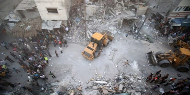 A digger removes the rubble of the Ghanam family home after it was targeted in an Israeli air raid on Rafah, in the southern of Gaza strip , on July 11, 2014.  Five Palestinians, including a woman and seven-year-old child, died when the militant's house in Rafah in southern Gaza was hit, and 15 other people were wounded, Gaza emergency services spokesman Ashraf al-Qudra said. AFP PHOTO / SAID KHATIB        (Photo credit should read SAID KHATIB/AFP/Getty Images)