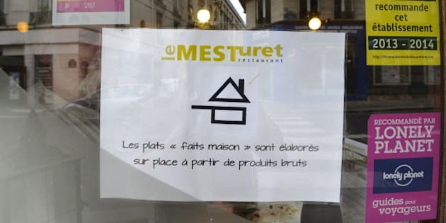 A photo taken on July 15, 2014 shows the new logo of a 'homemade' designation ('fait maison' in French) taped on the window of the 'Le Mesturet' restaurant in Paris, on the day a decree relating to the 'homemade' designation takes effect. A decree relating to the 'homemade' designation was passed on July 13 in France and took effect on July 15.  Sign reads: 'Dishes are 'homemade,' elaborated on the premises from unprocessed ingredients.'   AFP PHOTO / MIGUEL MEDINA        (Photo credit should read MIGUEL MEDINA/AFP/Getty Images)