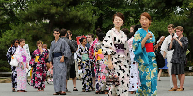HIMEJI, JAPAN - JUNE 22:  Japanese women dressed in Yuakata, a summer kimono ,walk as foreigners dressed in Yukata take photographs during the annual Himeji Yukata Festival on on June 22, 2014 in Himeji, Japan. Yukata is a casual summer version of kimono, traditionally made of cotton instead of silk. The Himeji Yukata Festival was started by Himeji lord Sakakibara Masamune over 250 years ago.  (Photo by Buddhika Weerasinghe/Getty Images)