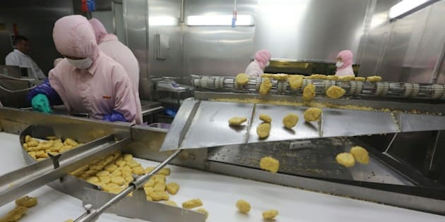 This picture taken on July 20, 2014 shows workers producing food at the Shanghai Husi Food Co., a factory of US food provider OSI Group, in Shanghai.  Shanghai city officials have shut a Shanghai Husi factory of US food provider OSI Group for selling out-of-date meat to restaurant giants including McDonald's and KFC, authorities said on July 21 in China's latest food safety scandal.    CHINA OUT     AFP PHOTO        (Photo credit should read STR/AFP/Getty Images)