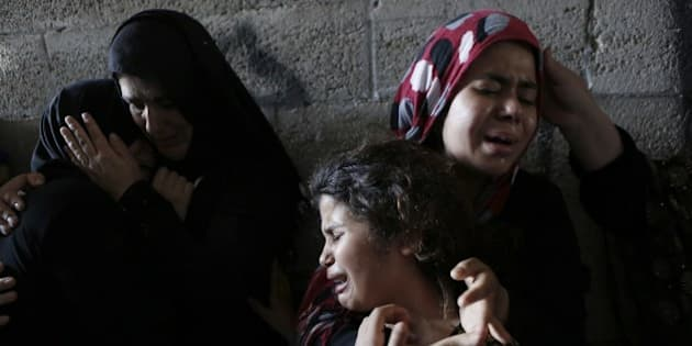 The daughters (R) of Hasan Baker, 60-years-old, grieve during his funeral in Gaza City, on July 22, 2014. A series of Israeli air strikes early killed seven people in Gaza, including five members of the same family, emergency services spokesman Ashraf al-Qudra said. The deaths hike the total Palestinian toll to 583 since the Israeli military launched Operation Protective Edge on July 8 in a bid to stamp out rocket fire from Gaza. AFP PHOTO / MOHAMMED ABED        (Photo credit should read MOHAMMED ABED/AFP/Getty Images)