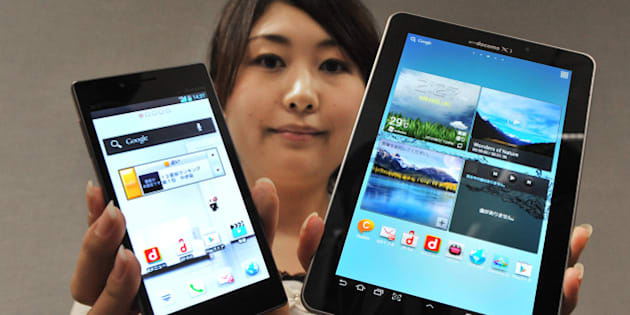 A model displays a new high-spec smartphone 'Optimus G L-01E' (L) and the world's largest organic EL display at 7.7 inches tablet 'GALAXY Tab 7.7 Plus SC-01E' (R) by Japanese mobile phone carrier NTT DoCoMo during a press preview in Tokyo on August 28, 2012. NTT DoCoMo unveiled three new smartphones and two new tablets, all compatible with the company's Xi LTE mobile service, for launch in or after September.   AFP PHOTO / KAZUHIRO NOGI        (Photo credit should read KAZUHIRO NOGI/AFP/GettyImages)