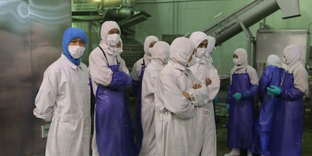 This picture taken on July 20, 2014 shows workers standing aside as inspectors investigate the Shanghai Husi Food Co., a factory of US food provider OSI Group, in Shanghai.  Shanghai city officials have shut a Shanghai Husi factory of US food provider OSI Group for selling out-of-date meat to restaurant giants including McDonald's and KFC, authorities said on July 21 in China's latest food safety scandal.    CHINA OUT     AFP PHOTO        (Photo credit should read STR/AFP/Getty Images)