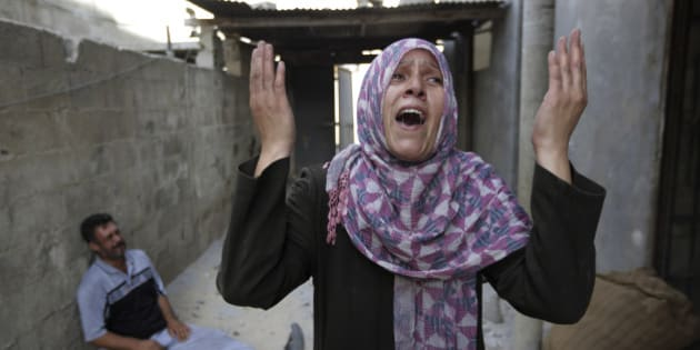 As her brother-in-law Mazen Keferna, background left, weeps, Palestinian Manal Keferna, 30, right, cries upon her return to the family house, destroyed by Israeli strikes in Beit Hanoun, northern Gaza Strip, Saturday, July 26, 2014. Thousands of Gaza residents who had fled Israel-Hamas fighting streamed back to devastated border areas during a lull Saturday, and were met by large-scale destruction: scores of homes were pulverized, wreckage blocked roads and power cables dangled in the streets. (AP Photo/Lefteris Pitarakis)