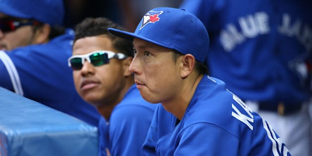 TORONTO, CANADA - JUNE 29: Munenori Kawasaki #66 of the Toronto Blue Jays looks on from the dugout next to Marcus Stroman #54 during MLB game action against the Chicago White Sox on June 29, 2014 at Rogers Centre in Toronto, Ontario, Canada. (Photo by Tom Szczerbowski/Getty Images)