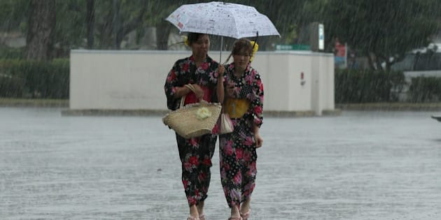 HIMEJI, JAPAN - JUNE 22:  Japanese women dressed in 'Yukata' summer kimono's walk in a heavy rain during the annual Himeji Yukata Festival on June 22, 2014 in Himeji, Japan. Yukata is a casual summer version of kimono, traditionally made of cotton instead of silk. The Himeji Yukata Festival was started by Himeji lord Sakakibara Masamune over 250 years ago.  (Photo by Buddhika Weerasinghe/Getty Images)