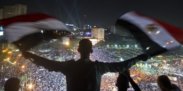 A Egyptian man waves national flags as an army helicopter flies over supporters of Egyptian Armed Forces General Ahmed Fattah al-Sisi rallying at Tahrir Square in Cairo on July 26, 2013. Egypt formally detained Mohamed Morsi for allegedly abetting militants in murdering policemen and staging prison escapes, as clashes during massive rallies by his opponents and loyalists killed five people. AFP PHOTO / KHALED DESOUKI        (Photo credit should read KHALED DESOUKI/AFP/Getty Images)
