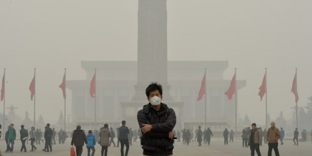 A Chinese tourist wears a face mask in Tiananmen Square as heavy air pollution continues to shroud Beijing on February 26, 2014. Beijing's official reading for PM 2.5, small airborne particles which easily penetrate the lungs and have been linked to hundreds of thousands of premature deaths, stood at 501 micrograms per cubic metre.   AFP PHOTO/Mark RALSTON        (Photo credit should read MARK RALSTON/AFP/Getty Images)