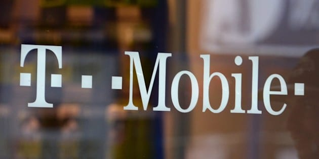 A patron exits a T-Mobile store in Glendale, California, on August 1, 2014. Shares in T-Mobile jumped on July 31 on a report that French telecommunications firm Iliad is bidding to buy the US wireless service carrier.   AFP PHOTO / Robyn Beck        (Photo credit should read ROBYN BECK/AFP/Getty Images)