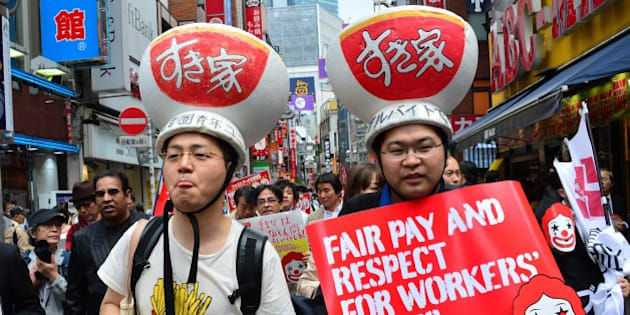 Labour union members wearing gear of Sukiya fast-food beef-bowl restaurant hold placards to demand payment of 1,500 yen (15 USD) an hour for part-time jobs during a march in Tokyo on May 15, 2014. Some 50 activists joined the global action to ask higher pay for part-time workers.  AFP PHOTO / Yoshikazu TSUNO        (Photo credit should read YOSHIKAZU TSUNO/AFP/Getty Images)