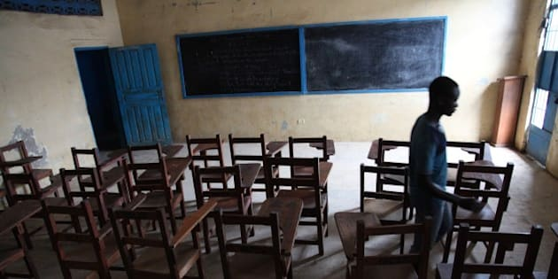 A boy walks on July 31, 2014 through an empty class room in a school in Monrovia which has been closed down by the Liberian government like all schools through out the country to protect students from contracting Ebola. Liberia announced on July 30 it was shutting all schools and placing 'non-essential' government workers on 30 days' leave in a bid to halt the spread of the deadly Ebola epidemic raging in west Africa. The impoverished country, along with neighbouring Guinea and Sierra Leone, is struggling to contain an epidemic that has infected 1,200 people and left 672 dead across the region since the start of the year. AFP PHOTO / STRINGER        (Photo credit should read STRINGER/AFP/Getty Images)