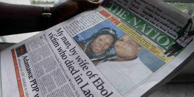 A man reads a newspaper featuring a front page story on the death of Liberian diplomat Patrick Sawyer (pictured with his wife Decontee) who died of the Ebloa virus in Lagos on July 30, 2014. Nigeria is on alert against the possible spread of Ebola after the first confirmed death from the virus in Lagos, Africa's biggest city and the country's financial capital. The victim, who worked for the Liberian government, collapsed at Lagos international airport after arriving on a flight from Monrovia via the Togolese capital Lome, according to the Nigerian government. Doctors Without Borders (MSF) warned that the crisis gripping Guinea, Liberia and Sierra Leone would only get worse and could not rule out it spreading to other countries. AFP PHOTO/PIUS UTOMI EKPEI        (Photo credit should read PIUS UTOMI EKPEI/AFP/Getty Images)