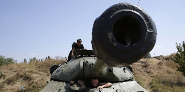 Servicemen are in the WWII Soviet tank IS-3 captured from pro-Russia militants at the position of the Ukrainian troops in Donetsk region on August 9, 2014. Fighting with pro-Russian separatists in eastern Ukraine has left 13 troops dead in the last 24 hours, Ukraine's military said Saturday. AFP PHOTO/ ANATOLII STEPANOV        (Photo credit should read ANATOLII STEPANOV/AFP/Getty Images)
