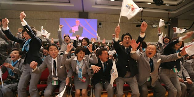 Japanese Prime Minister Shinzo Abe (3-R) celebrates alongside Tokyo 2020 delegation members after IOC president Jacques Rogge announced the Japanese capital to be the winner of the bid to host the 2020 Summer Olympic Games, during the 125th session of the International Olympic Committee (IOC), in Buenos Aires, on September 7, 2013. The three cities bidding to host the 2020 Summer Olympics -- Madrid, Istanbul and Tokyo -- delivered their final presentations ahead of the expected tight vote by the IOC, though Madrid was eliminated from the race moments after, in the first round of voting.    AFP PHOTO / YAN WALTON        (Photo credit should read YAN WALTON/AFP/Getty Images)