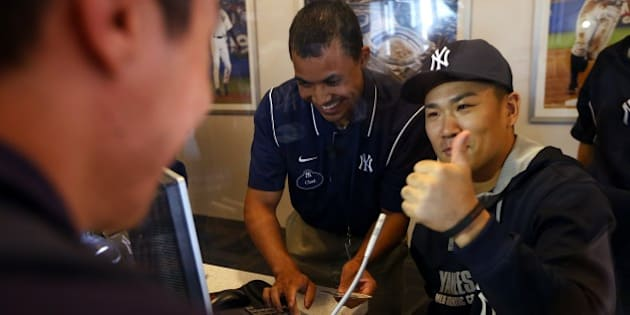 NEW YORK, NY - AUGUST 06: Pitcher Masahiro Tanaka #19 of the New York Yankees helps sell tickets in the advance ticket window before the start of their game against the Detroit Tigers at Yankee Stadium on August 6, 2014 in the Bronx borough of New York City. (Photo by Rich Schultz/Getty Images)