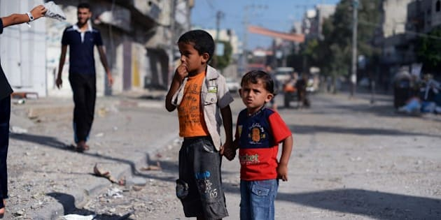 Two Palestinian boys hold hands as they look at the bombed out remains of a mosque that was targeted by Israeli air strikes at the Nuseirat refugee camp in the Central Gaza Strip early on August 10, 2014. Palestinian negotiators have warned they will leave Cairo on August 10 if their Israeli counterparts do not show up for truce talks, after Israel pummelled Gaza with fresh air strikes that killed at least 10 Palestinians.  AFP PHOTO/ROBERTO SCHMIDT        (Photo credit should read ROBERTO SCHMIDT/AFP/Getty Images)