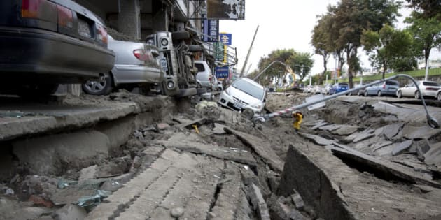 KAOHSIUNG, TAIWAN - AUGUST 01:  Vehicles lie on the damaged road after gas explosions in southern Kaohsiung on August 1, 2014 in Kaohsiung, Taiwan. A series of powerful gas blasts killed 25 people and injured up to 267 in the southern Taiwanese city of Kaohsiung, overturning cars and ripping up roads, officials said.  (Photo by Ashley Pon/Getty Images)