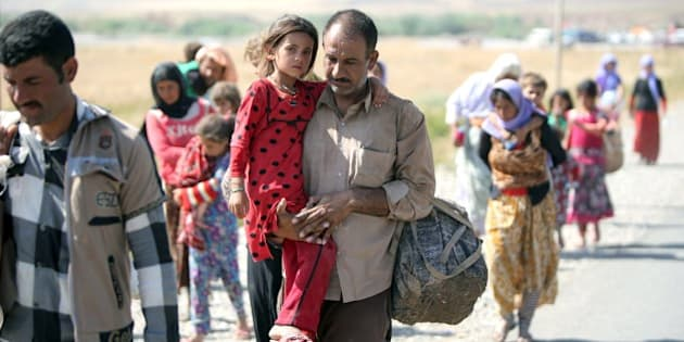 A displaced Iraqi man from the Yazidi community carries his daughter as they cross the Iraqi-Syrian border at the Fishkhabur crossing, in northern Iraq, on August 11, 2014. At least 20,000 civilians, most of whom are from the Yazidi community, who had been besieged by jihadists on a mountain in northern Iraq have safely escaped to Syria and been escorted by Kurdish forces back into Iraq, officials said. The breakthrough coincided with US air raids on Islamic State fighters in the Sinjar area of northwestern Iraq on August 9, and Kurdish forces from Iraq, Syria and Turkey working together to break the siege of Mount Sinjar and rescue the displaced. AFP PHOTO/AHMAD AL-RUBAYE        (Photo credit should read AHMAD AL-RUBAYE/AFP/Getty Images)