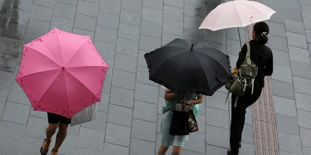 HIMEJI, JAPAN - AUGUST 10:  Women walk through strong rain and wind delivered by Typhoon Halong on August 10, 2014 in Himeji, Japan. The Japan Meteorological Agency has issued heavy rain and wind warnings. More than one million people have been advised to evacuate areas across of South-Western Japan.  (Photo by Buddhika Weerasinghe/Getty Images)