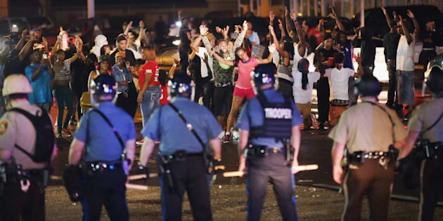 FERGUSON, MO - AUGUST 15:  Missouri State Highway Patrol officers listen to taunts from demonstrators during a protest over the death of Michael Williams on August 15, 2014 in Ferguson, Missouri. As the taunts became more aggressive the troopers called in the county police then left the area. County police Shot pepper spray,  smoke, gas and flash grenades at protestors before retreating. Several businesses were looted as the county police sat nearby with armored personnel carriers (APC). Violent outbreaks have taken place in Ferguson since the shooting death of Brown by a Ferguson police officer on August 9.  (Photo by Scott Olson/Getty Images)