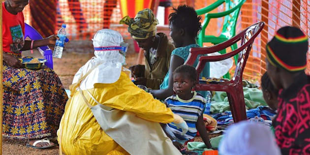 An MSF medical worker feeds an Ebola child victim at an MSF facility in Kailahun, on August 15, 2014. Kailahun along with Kenama district is at the epicentre of the world's worst Ebola outbreak. The World Health Organisation (WHO) revealed that the latest death toll from the Ebola virus in Guinea, Sierra Leone, Liberia and Nigeria had claimed more than1000  lives. Health Organizations are looking into the possible use of experimental drugs to combat the latest outbreak in West Africa. AFP PHOTO/Carl de Souza        (Photo credit should read CARL DE SOUZA/AFP/Getty Images)