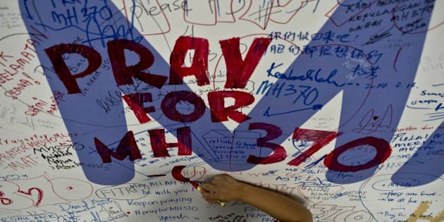 A Malaysia Airlines employee writes a message expressing prayers and well-wishes for passengers onboard missing Malaysia Airlines (MAS) flight MH370 at Kuala Lumpur International Airport in Sepang on March 14, 2014. The needle-in-a-haystack hunt for the missing Malaysian airliner spread to the vast Indian Ocean after the White House cited 'new information' that it might have flown for hours after vanishing nearly seven days ago.    AFP PHOTO/ MANAN VATSYAYANA        (Photo credit should read MANAN VATSYAYANA/AFP/Getty Images)